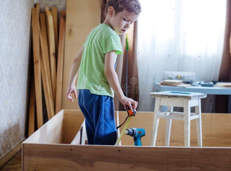 Jonge jongen die spoel gebruiken om houten boekenkast of plankeneenheid te meten stock fotografie
