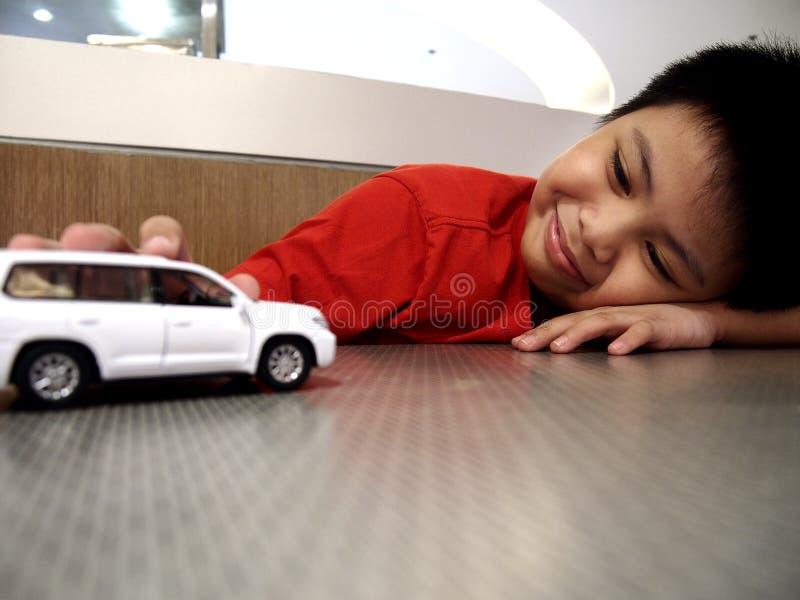 Jonge jongen die stuk speelgoed auto's bekijken stock afbeelding