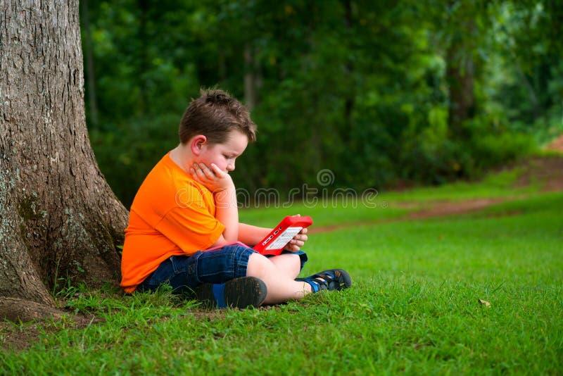 Jonge jongen die tablet in openlucht gebruiken royalty-vrije stock fotografie