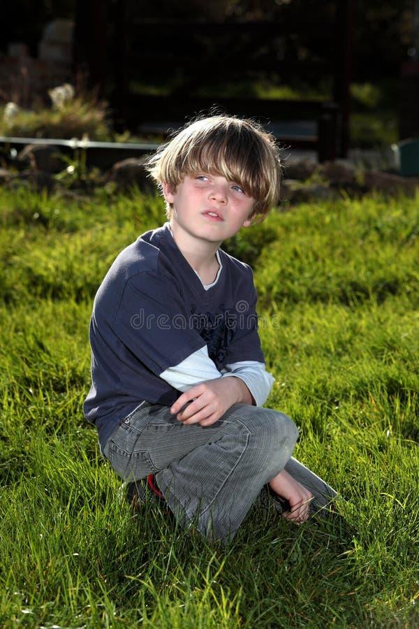 Jonge jongen die in tuin over zijn schouder kijken stock fotografie
