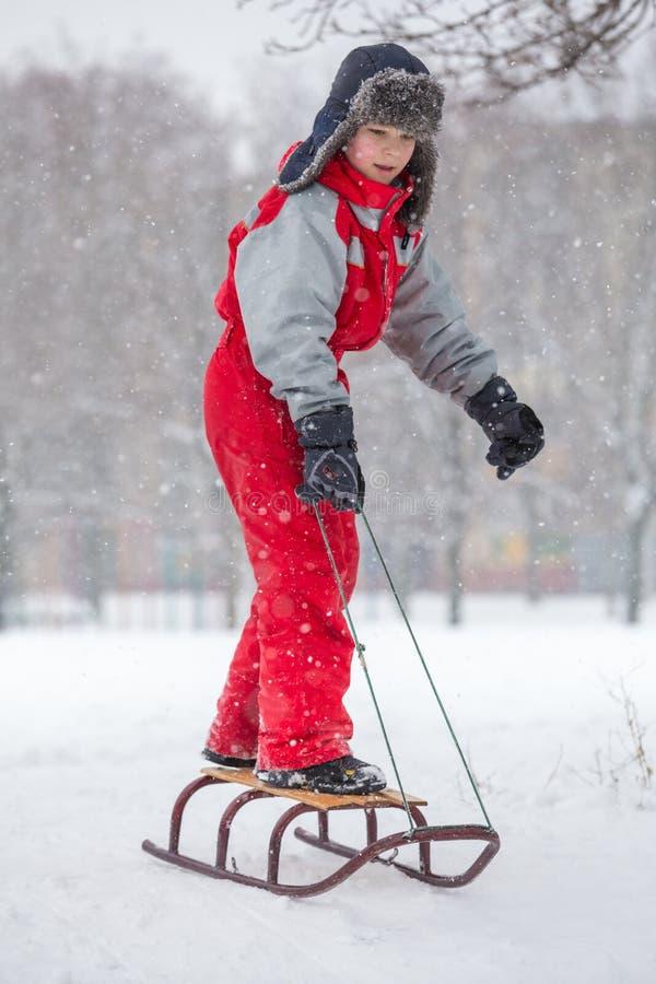 Jonge jongen die zich bij de dia op sneeuwheuvel bevinden royalty-vrije stock foto