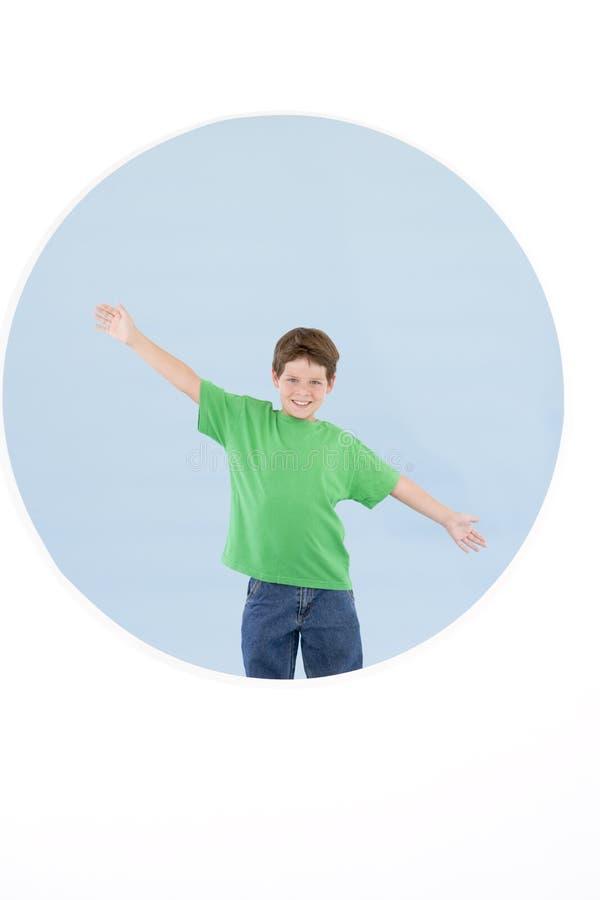 Jonge jongen die zich met wapens bevindt die uit glimlachen royalty-vrije stock afbeeldingen