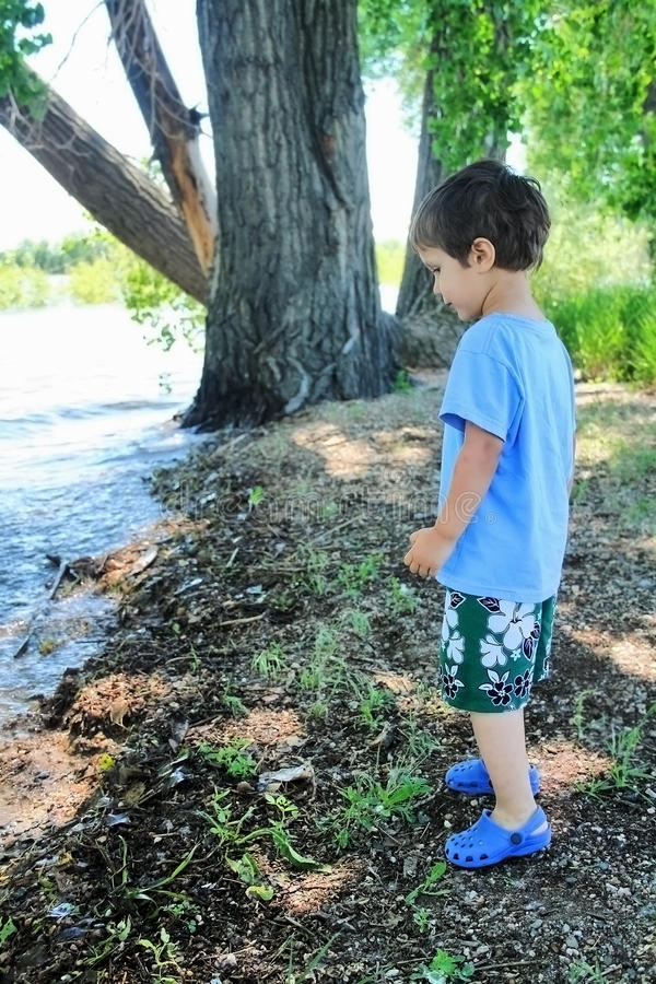 Jonge jongen die zich op de kust van een meer bevindt stock afbeelding