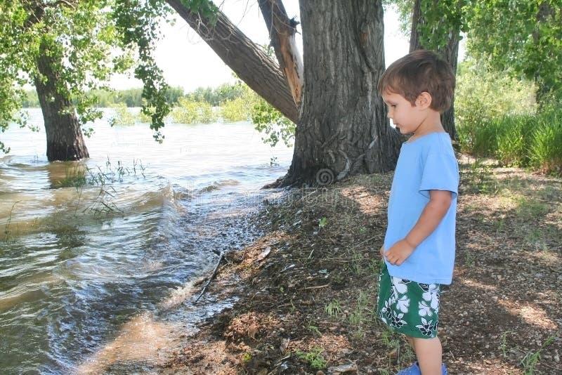 Jonge jongen die zich op de kust van een meer bevindt royalty-vrije stock foto's