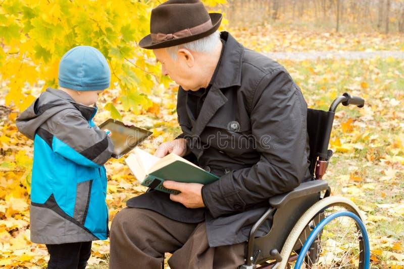 Jonge jongen die zijn grootvader zijn tablet tonen stock foto's