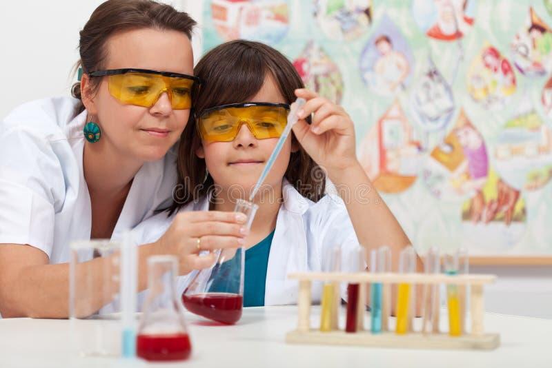 Jonge jongen in elementaire wetenschapsklasse die chemisch experiment doet royalty-vrije stock afbeeldingen