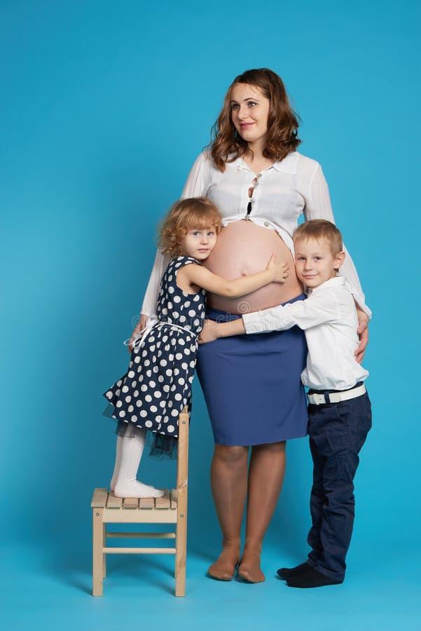 Jonge jongen en meisjesomhelzings zwangere moeder stock foto's