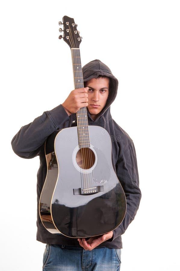 Jonge jongen in hoodie die en zijn gitaar bevinden zich houden stock foto