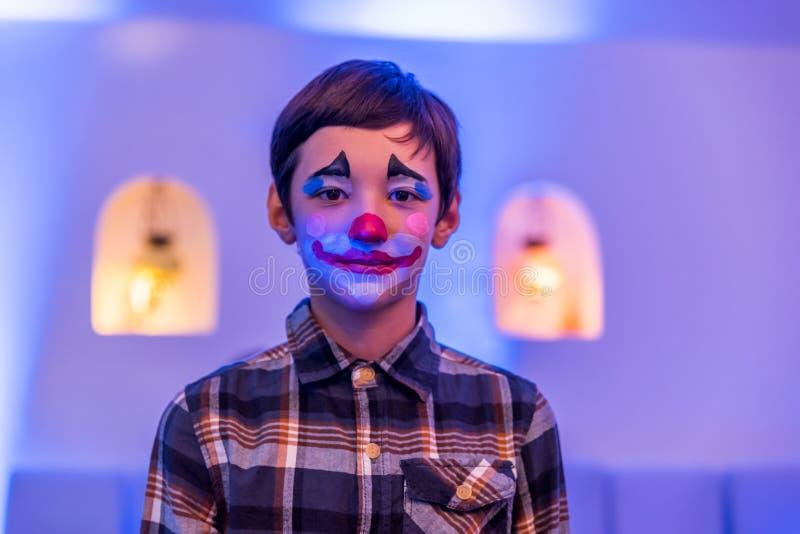 Jonge jongen met aquamake-up op gezicht stock foto's