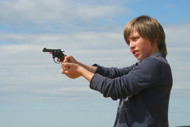 Jonge jongen met een stuk speelgoed pistool stock foto's