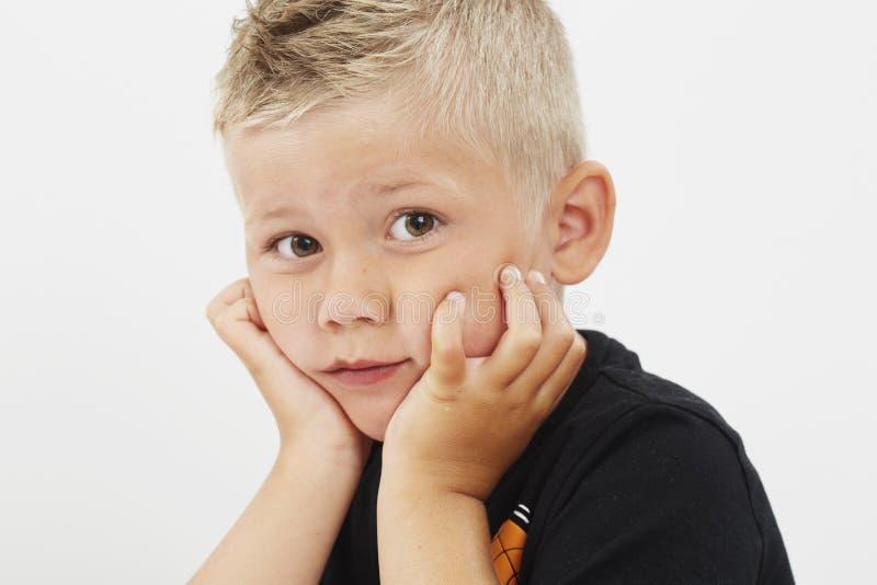 Jonge jongen met handen op kin stock foto