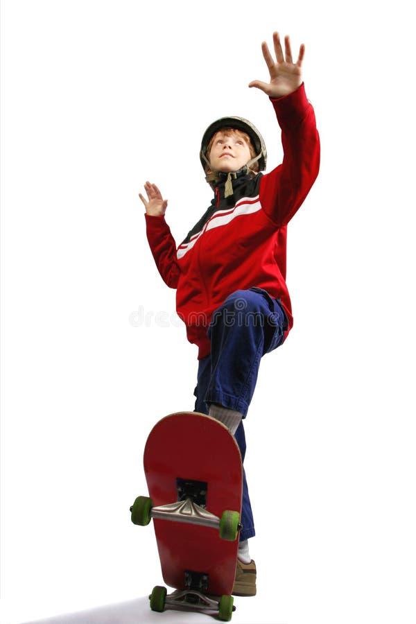 Jonge jongen met helm op skateboard stock fotografie