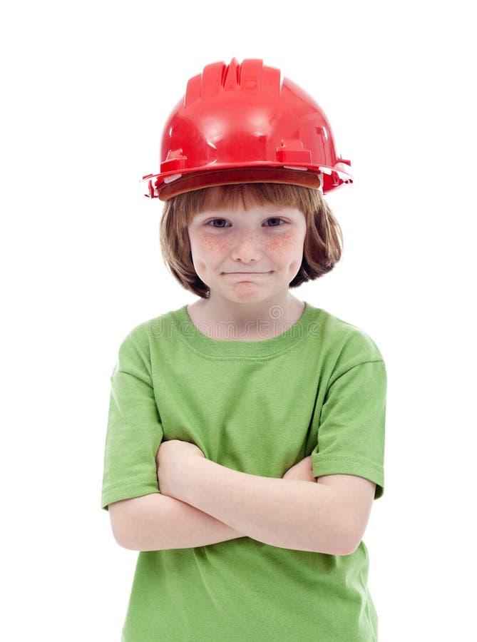Jonge jongen met rode bouwvakker stock fotografie