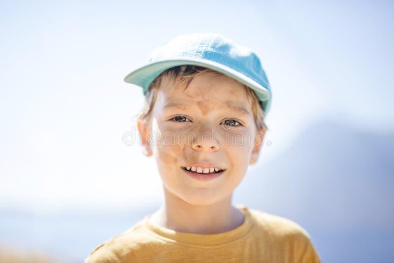 Jonge jongen met met vuile smudges op gezicht na in openlucht het spelen stock foto