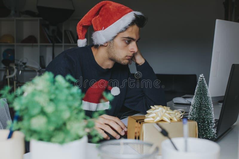 Jonge jongen op computer die Kerstmanhoed dragen stock afbeeldingen