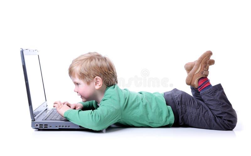 Jonge jongen op laptop stock foto