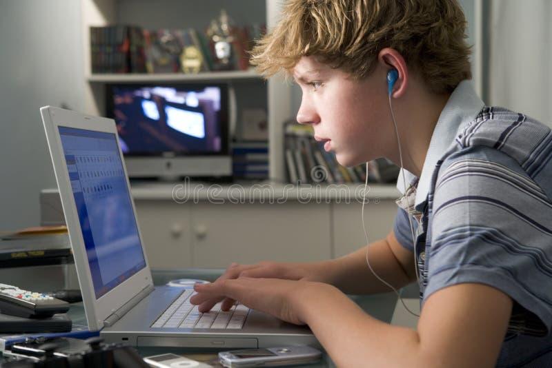 Jonge jongen in slaapkamer die laptop met behulp van die aan mp3 luistert stock foto