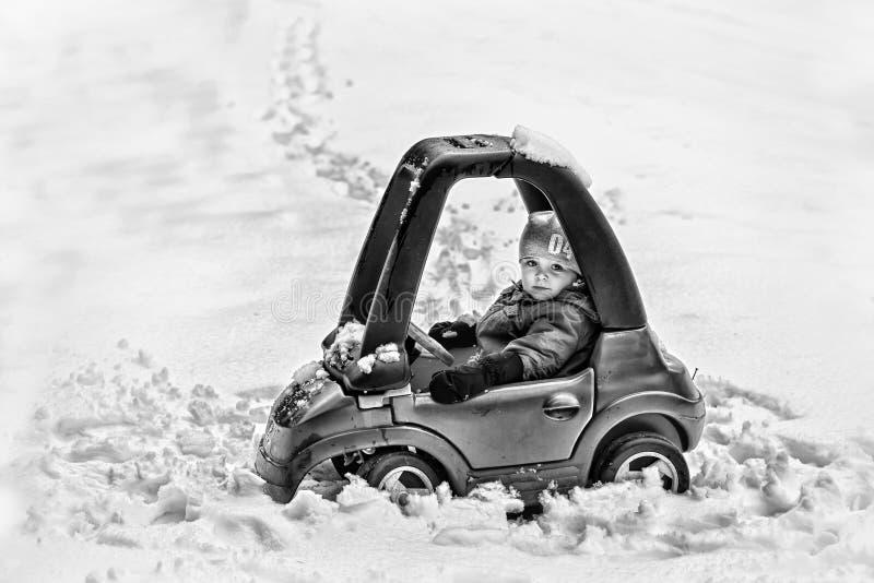 Jonge Jongen in Toy Car Stuck in de Zwart-witte Sneeuw - stock afbeelding