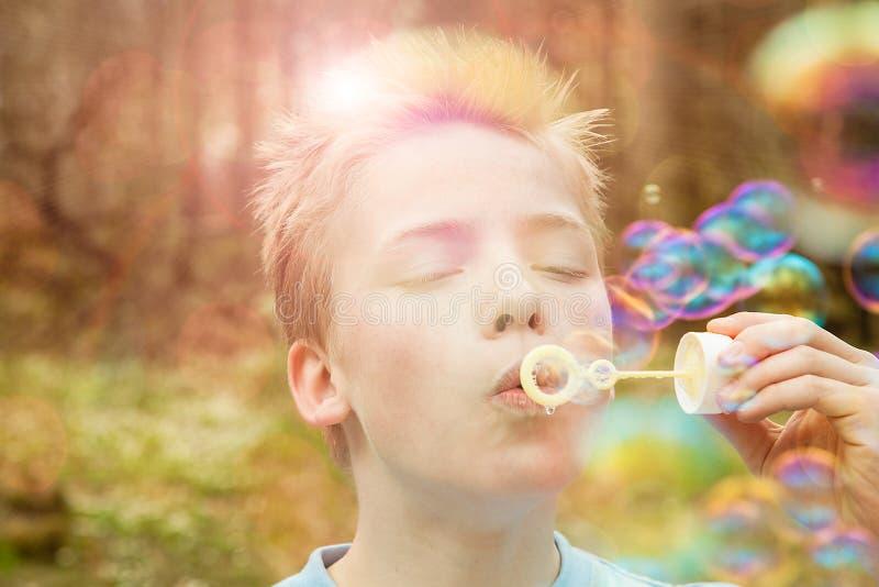 Jonge jongens blazende zeepbels in openlucht stock fotografie