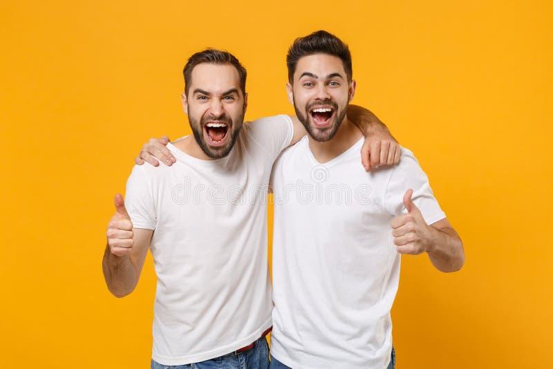 Jonge jongens vrienden in blanke lege t-shirts die geïsoleerd staan op de gele oranje achtergrond studio royalty-vrije stock foto