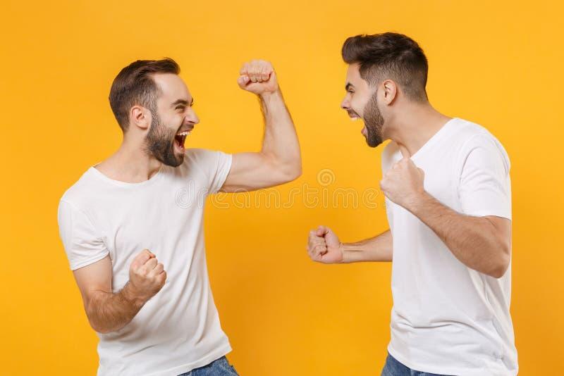 Jonge jongens vrienden in witte lege t-shirts die zich op gele oranje wand-achtergrond bevinden Mensen royalty-vrije stock fotografie