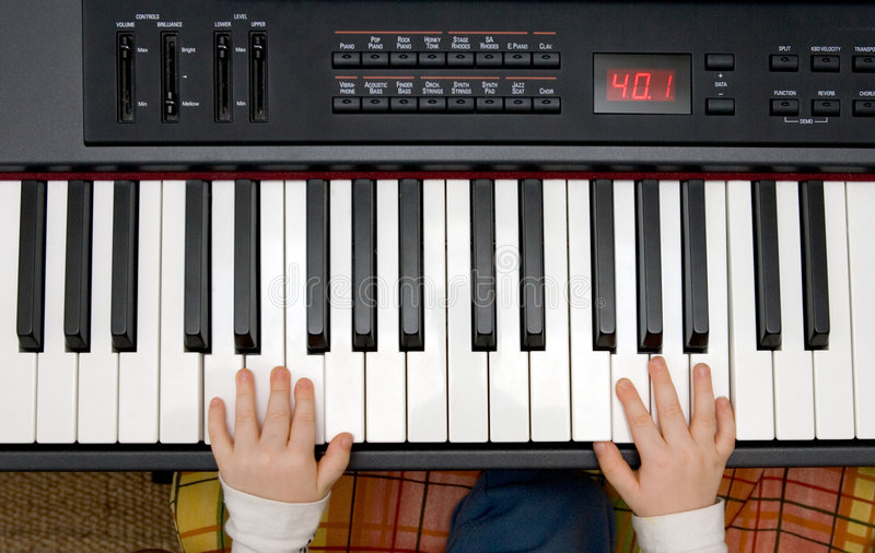 Jonge jongenshanden op een elektronisch piano of een toetsenbord stock foto's