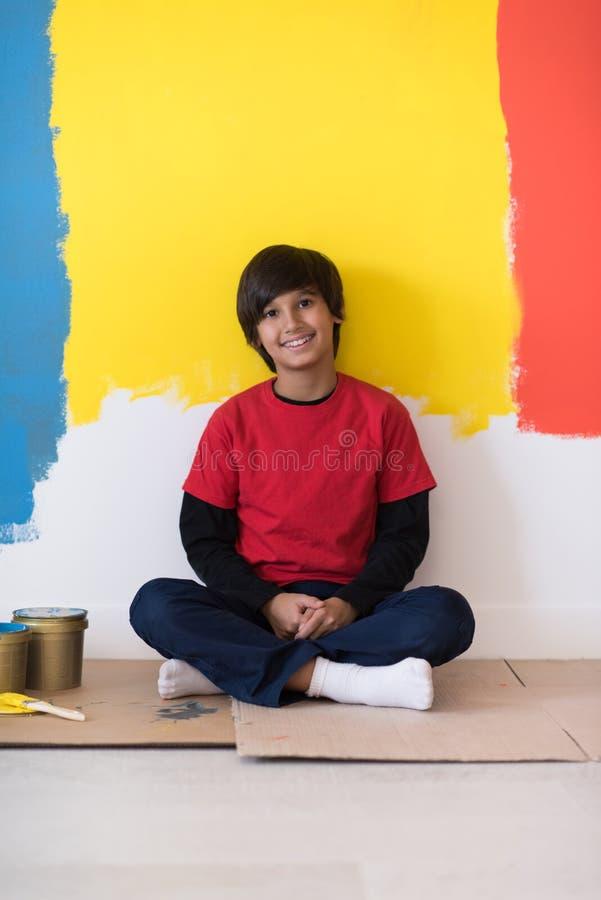 Jonge jongensschilder die na het schilderen van de muur rusten stock afbeeldingen