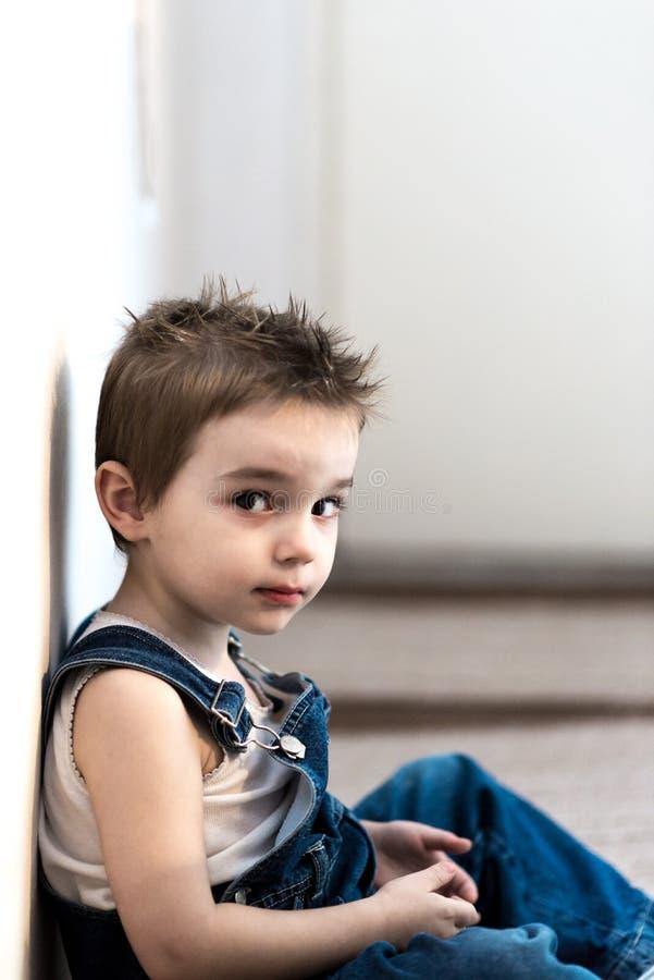 Jonge jongenszitting door de muur stock foto