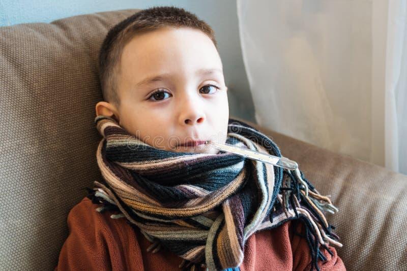 Jonge jongenszitting op de bank Zieke kind wachtende arts om hem te bezoeken Griep, de pediatrische dienst thuis Medisch concept  royalty-vrije stock foto's