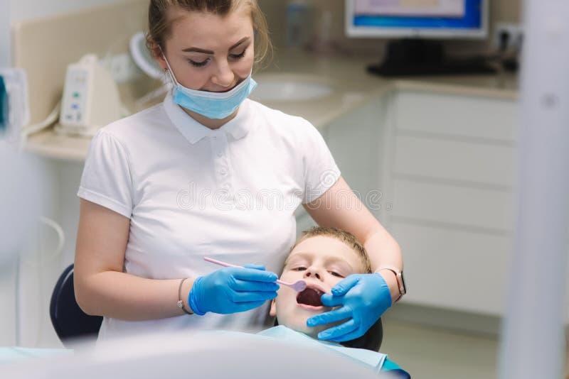 Jonge jongenszitting op de tandstoel op het kantoor De melktanden van het de tandartsonderzoek van kinderen royalty-vrije stock foto's
