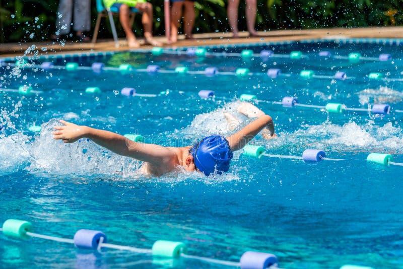 Jonge jongetswimmer die een vlinderslag maakt in een zwembad stock afbeelding