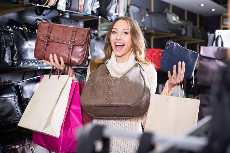 Jonge joyous vrouw het kopen leerbeurs in winkel stock foto's