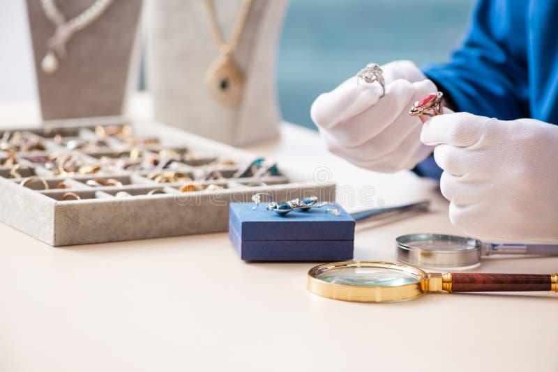 Jonge juwelier die in zijn workshop werkt stock afbeeldingen