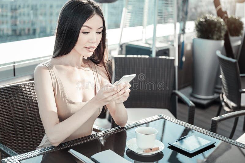 Jonge kalme cellphone van de meisjesholding en het bekijken het scherm stock fotografie