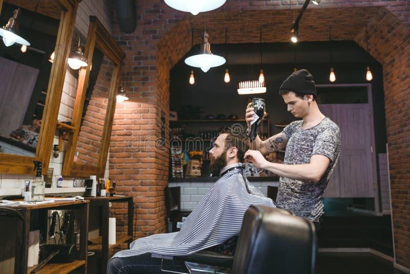 Jonge kapper die man haar met blowdryer drogen stock afbeeldingen