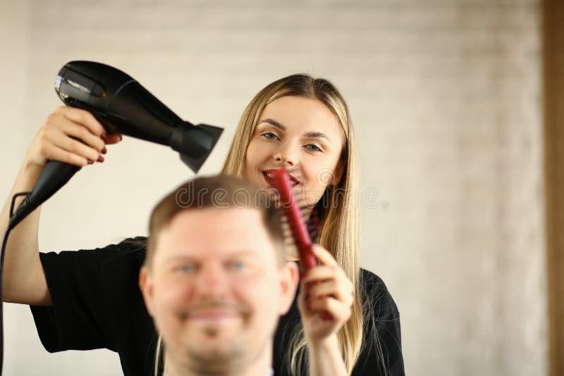 Jonge Kapper Drying Male Hair door Slagdroger royalty-vrije stock afbeelding