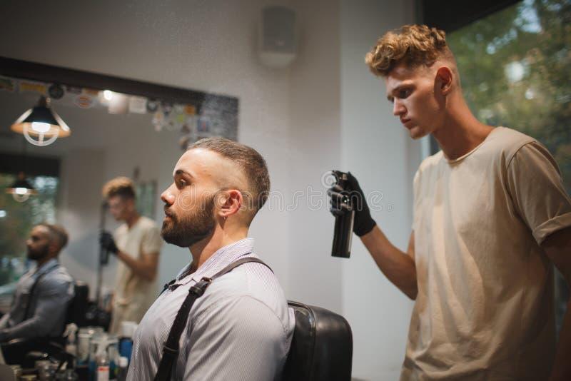 Jonge kapper met een haarlak die aan een vage achtergrond werken Modieuze cliënt in het concept van het de Kappersberoep van de k stock fotografie