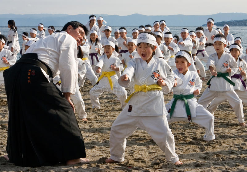 Jonge karatestudenten die op een strand presteren stock afbeelding