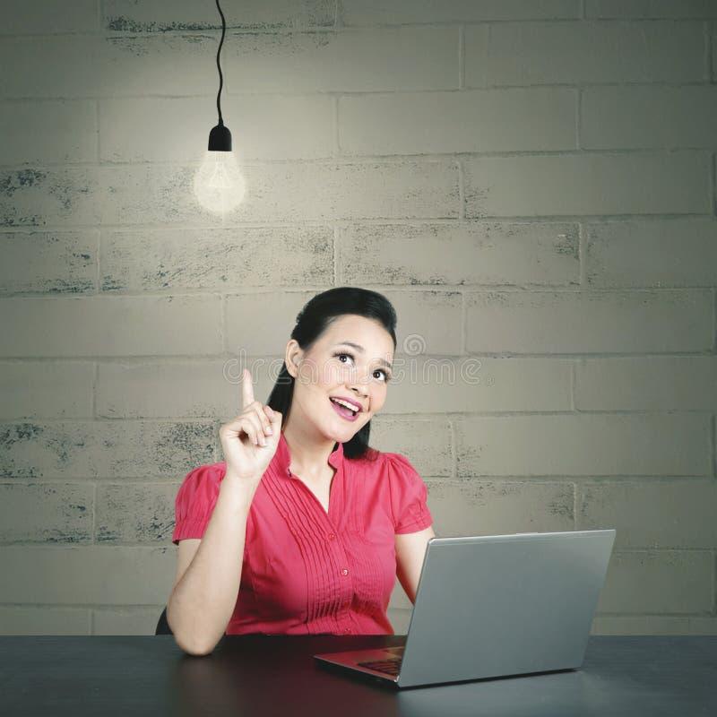 Jonge Kaukasische bedrijfsvrouw die haar ahaogenblik met gloeilamp hebben royalty-vrije stock foto's