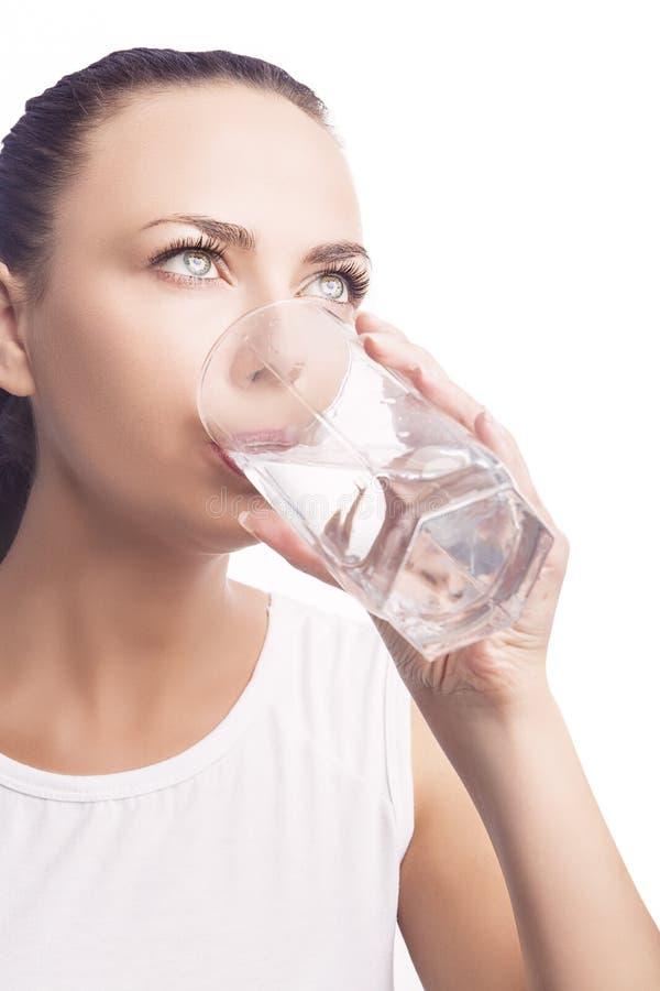 Jonge Kaukasische Dame Drinking Water van Glas De status isoleert royalty-vrije stock afbeelding
