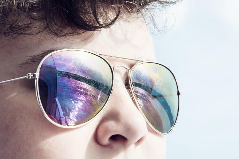 Jonge Kaukasische jongen met het weerspiegelen van brug in zonnebril stock foto