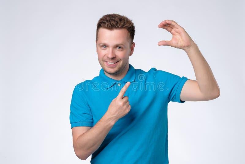 Jonge Kaukasische mens die in blauw overhemd op lege plaats voor uw kaart of advertentie richten stock foto's