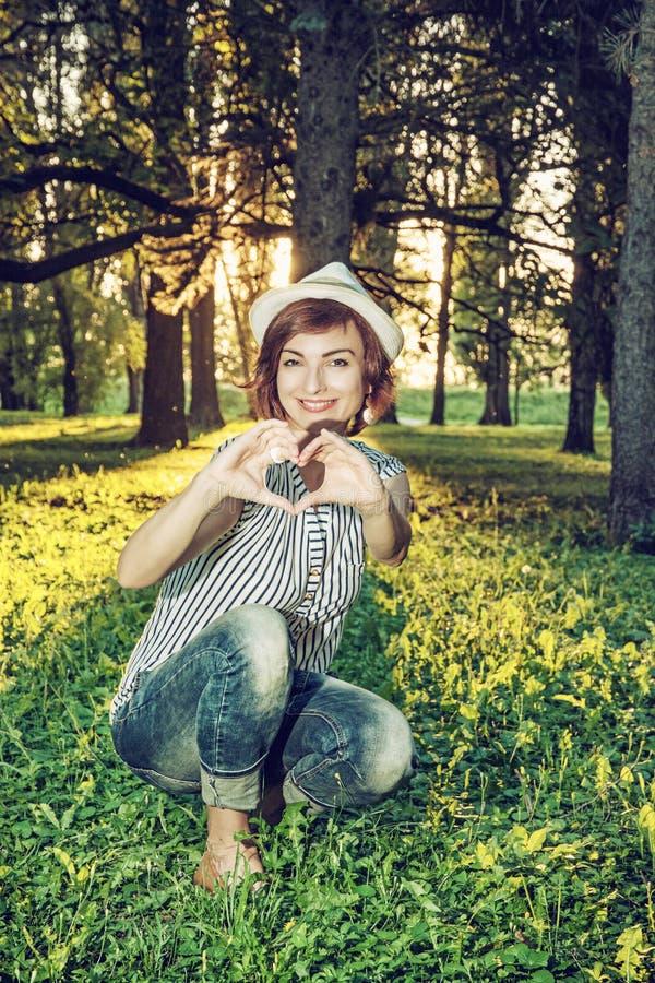 Jonge Kaukasische natuurlijke vrouw die hartvorm, retro fotofi maakt royalty-vrije stock afbeeldingen