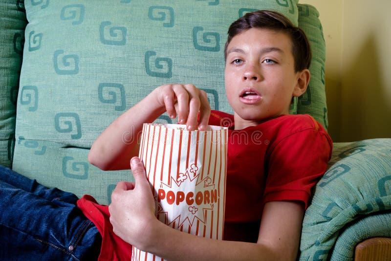 Jonge Kaukasische tiener die op een enge film letten stock fotografie