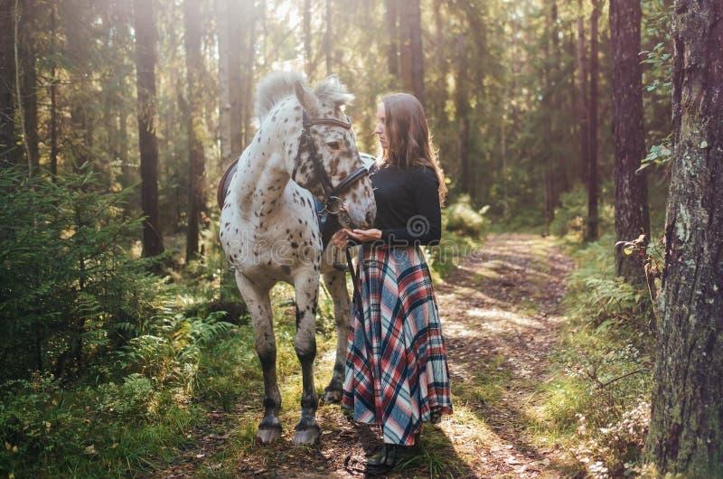 Jonge Kaukasische vrouw die haar paard behandelen, die in bos lopen royalty-vrije stock foto's