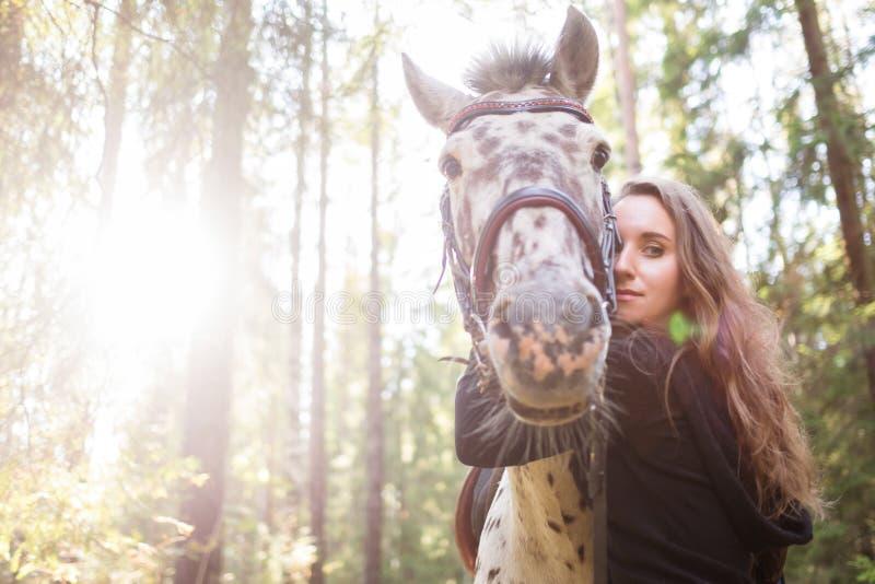 Jonge Kaukasische vrouw die haar paard behandelen, die zijn hals koesteren stock foto