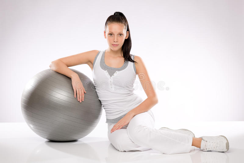 Jonge Kaukasische vrouw die op geschiktheidsbal leunen stock foto