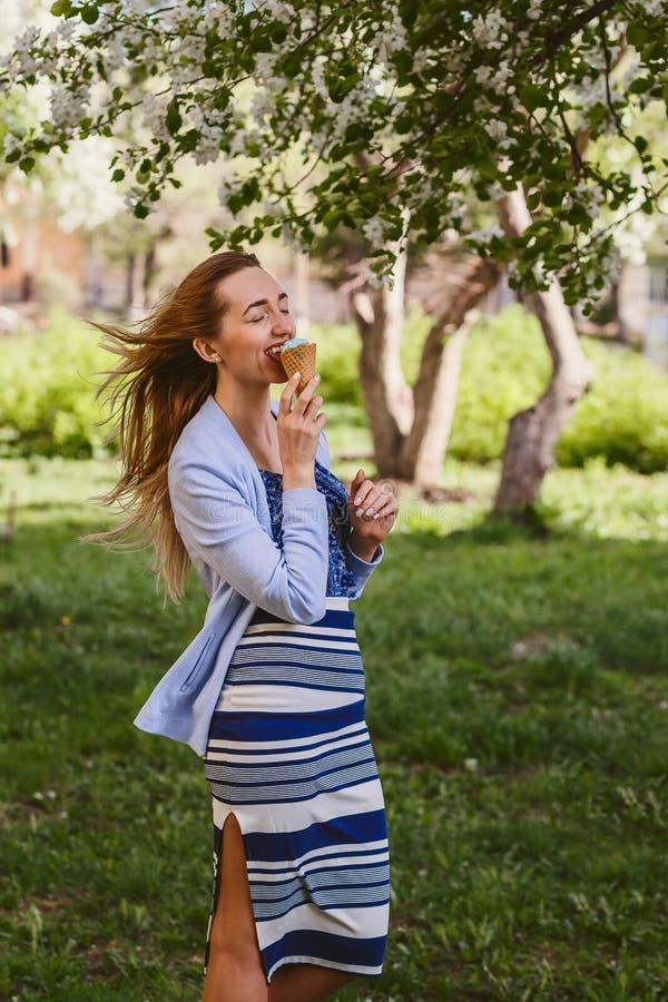 Jonge Kaukasische vrouw die roomijs in openlucht in de lente eten Het genieten van de van smaak stock afbeeldingen