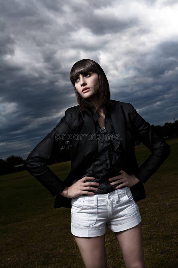 Jonge Kaukasische vrouw in een park met stormachtige hemel stock foto's