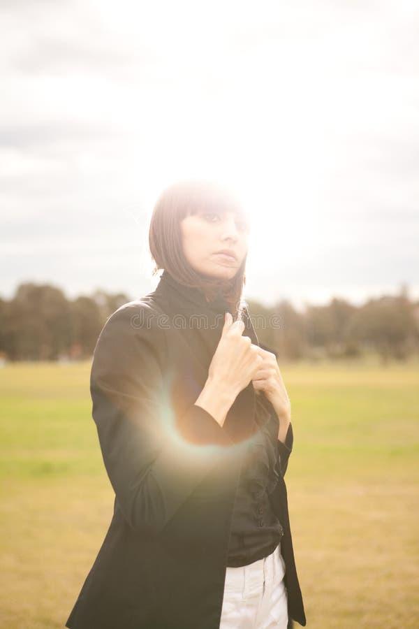 Jonge Kaukasische vrouw in een park met zon het glanzen royalty-vrije stock fotografie